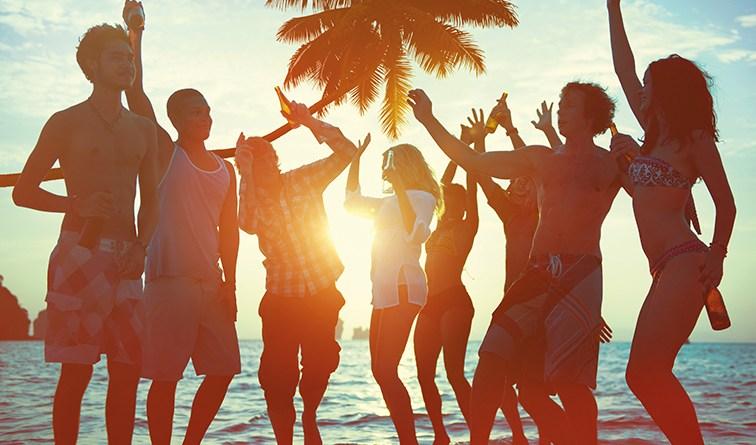Gruppe junger Leute am Strand beim feiern. Sonnenuntergang. Palme. Meer. Maturareise