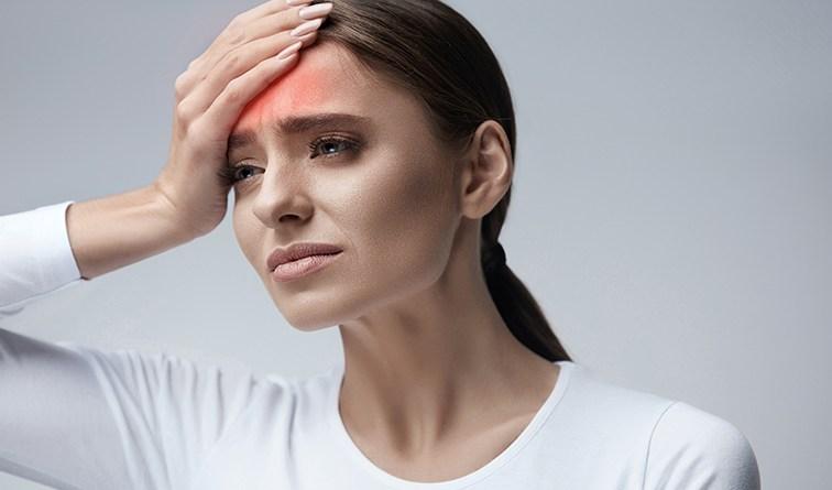 Frau hat Kopfschmerzen. Frau in weißem Oberteil greift sich auf den Kopf