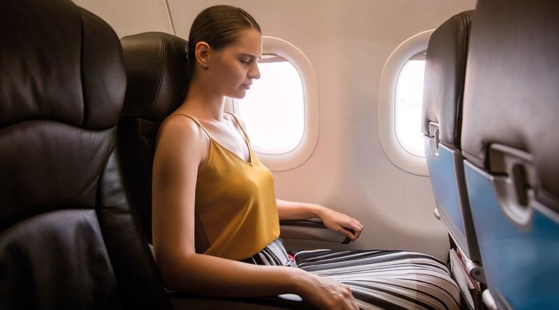 Frau sitzt im Flieger und ist konzentriert. Flugangst was tun