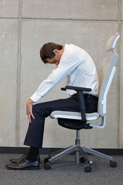 Mann auf Bürostuhl macht Katzenbuckel. Rückenschmerzen Übungen
