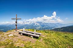 Gipfelkreuz und Bank auf Berg. Wandertipps