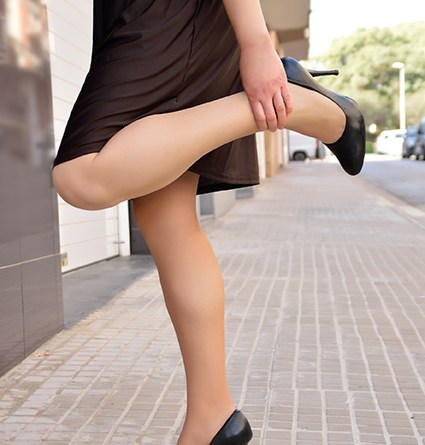 Frau greift sich an Bein und winkelt Knie ab. Gesundheitsratgeber im September