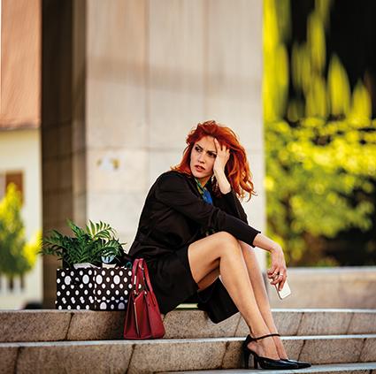 Frau mit roten Haaren und Rock sitzt auf Steintreppe im Freien. Sieht verzweifelt aus. verkühlte Blase