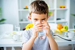 Bub trinkt Wasser aus Glas. Fit für die Schule