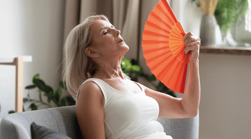 Frau sitzt auf Couch und wedelt mit Fächer Luft zu. Frau hat Hitzewallungen. Hitzeschübe