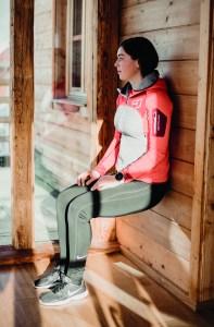 Frau trainiert Wandsitz an Holzwand. Übungen fürs Skifahren Vorbereitung