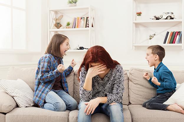 Mutter sitzt verzweifelt auf Sofa während beide Kinder schreien. gestresste Mutter. Stressbewältigung