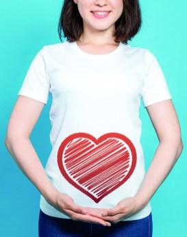 Frau ohne Bauchschmerzen. Frau in weißem T-Shirt. Frau mit Herz am Buch. Darm im Gleichgewicht. Reizdarmsyndrom