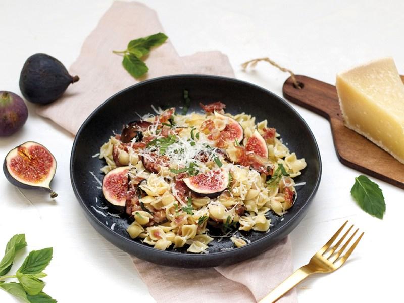 Low Carb Rezepte. Cavatelli mit Pancetta, Feigen und Pecorino in schwarzer Pfanne auf hellem Hintergrund. goldenes Besteck