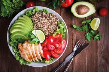 Gesunde Mahlzeit aus Avocado, Tomaten, Salat, Huhn und Körnern. Regeneration nach dem Sport. Gericht in Schüssel auf Holztisch