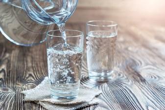 Zwei Gläser Wasser auf Holztisch. Wasser aus Glaskrug wird in Glas geleert. Frisches Wasser. Regeneration nach dem Sport
