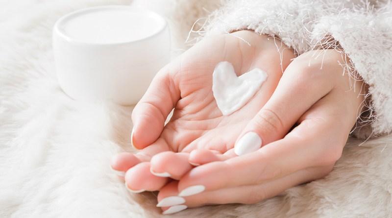 Schöne, gesunde Hände. Herz aus Creme auf Händen. schützende Hautpflege. Cremetiegel.