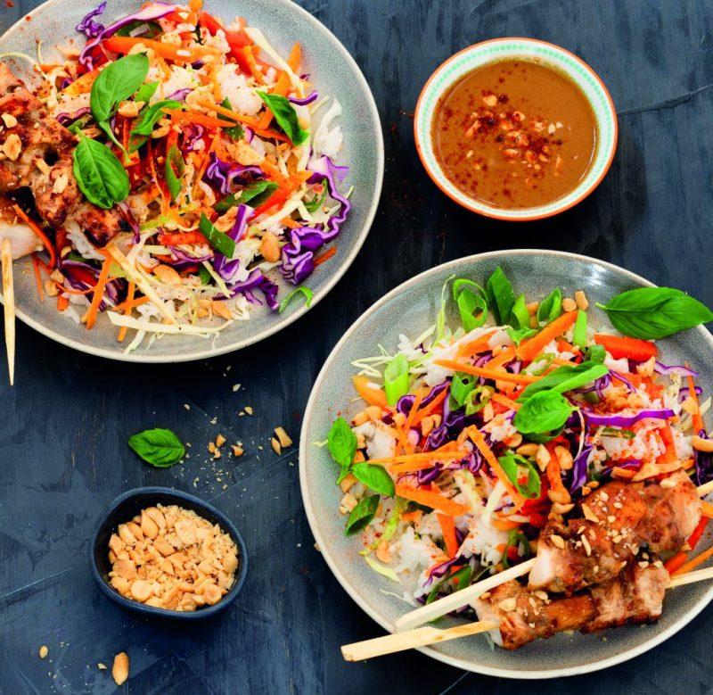 Bunter Reissalat mit Hähnchenspießen und Erdnuss-Dressing angerichtet in zwei Schüsseln auf dunklem Hintergrund. Clean Eating