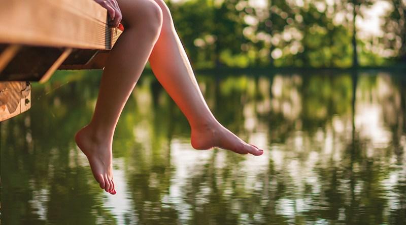 Frauenbeine baumeln von Steg. See. Sommer. Frühling. Venen. Unterschenkel