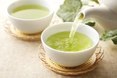 Grüner Tee. Tee in weißen Tassen. Tee ausgießen. Detox