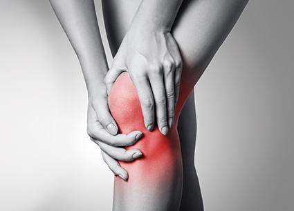 Kniegelenk in schwarz weiß. Rotes Knie. Frau hält sich Knie. Schmerzendes Knie. Gelenkschmerzen
