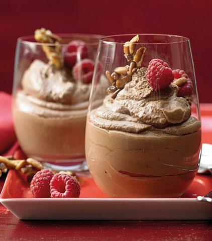 Soul Food. Mousse au Chocolate mit Pinienkern-Krokant und Himbeeren angerichtet in Gläsern