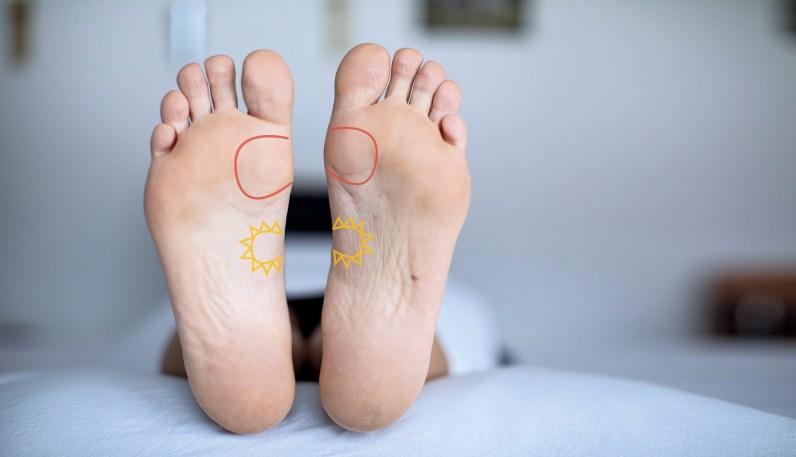 Füße einer Frau. Frau liegt. Fußreflexzonenmassage Herz eingezeichnet
