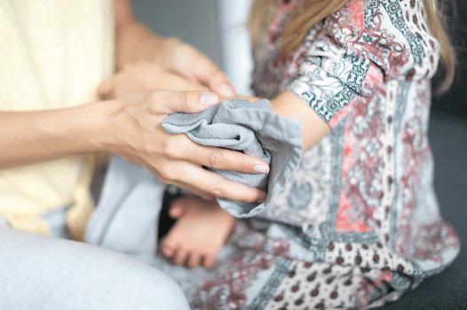 Frau gibt Topfenwickel in grauem Tuch auf Hand von Kind. Insektenstich. Insektenstich Hausmittel