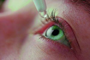 grünes Auge. Frau tropft Auge ein. Augentropfen. Augengesundheit Bildschirmarbeit. Trockene Augen, brennende Augen