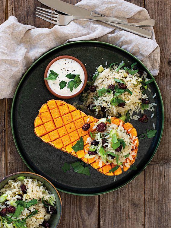 Gefüllte Butternusskürbisse mit Reis und Ziegenkäse-Sauce angerichtet auf schwarzem Teller auf Holztisch. Herbstgerichte