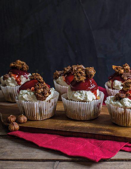 Kürbis-Haselnuss- Cupcakes mit Zwetschken angerichtet auf Holzbrett mit Schwarzem Hintergrund. Kürbis. Zwetschken. Herbstgerichte