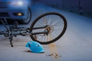 Fahrradunfall. Nachtblindheit. Dämmerung. Auto kommt, Fahrrad liegt. Fahrradhelm am Boden