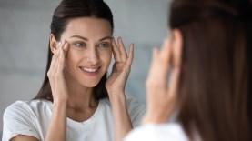 Frau sieht in Spiegel und massiert Augenhöle. Augenschonen. Nachtblindheit
