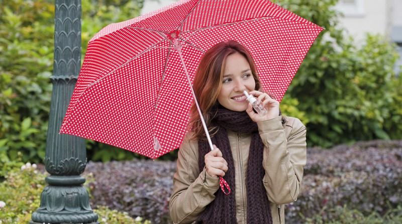 Frau mit Nasenspray in der Hand. Frau sprüht Nasenspay in Nase. Frau im Freien mit rotem Regenschirm mit weißen Tupfen. verstopfte Nase