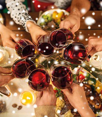 Familie stoßt mit Wein auf Weihnachten an. Weihnachtsspeck loswerden. weihnachtlich dekorierter Tisch