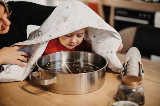 Kind über Topf mit Handtuch. Inhalation mit Thymian. inhalieren. Hausmittel gegen Husten