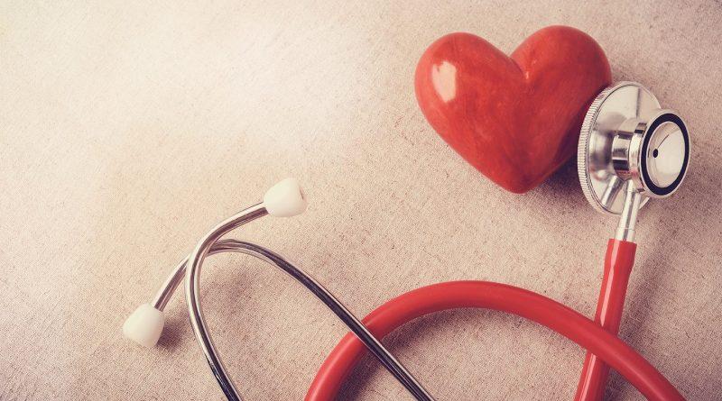 Stetoskop auf Herz auf beigem Untergrund. Cholesterinspiegel