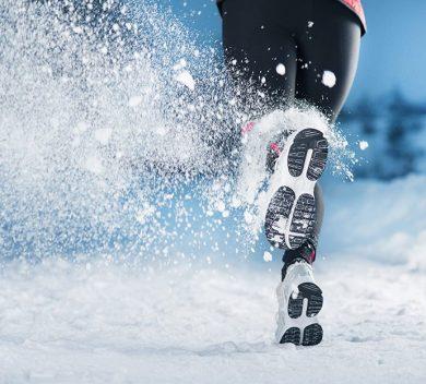 Läuferin im Winter. Beine einer Frau. Schnee. Blutstauung in den Venen