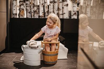 Kind nimmt Fußbad. Ansteigendes Fußbad. Kind ist bis zu Knöcheln in warmem Wasser. Hausmittel gegen Schnupfen