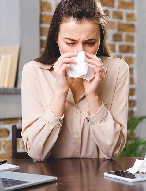 Frau im Büro mit Taschentuch. Allergie. Frau schäuzt sich. Atemprobleme