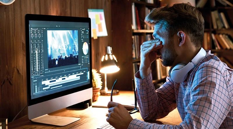 Mann mit Augenschmerzen. Mann sitzt vor Bildschirm und reibt sich die Augen. Homeoffice-Eye-Syndrom