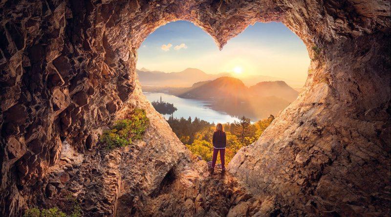 Frau steht in herzförmiger Höle und genieß die Berglandschaft. Sonnenaufgang. Gesundes Herz