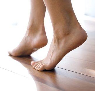 schöne, gepflegte Füße gehen über Parkettboden. Hyaluron Activ Fußcreme