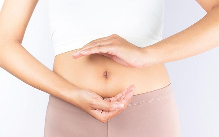 Closeup von einem Bauch. Darm in Balance. Hande vor Bauch. Heller Hintergrund. Darum und Immunabwehr