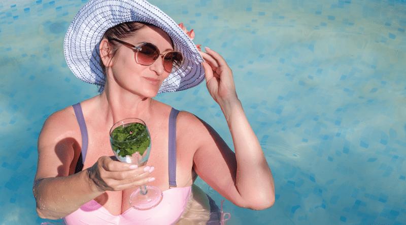 Ältere Frau im rosa Bikini mit lila Sonnenhut im Pool. Cocktail in Hand. Ältere Frau. Sommer. Hitzewallung. Abkühlung. Phasen der Wechseljahre