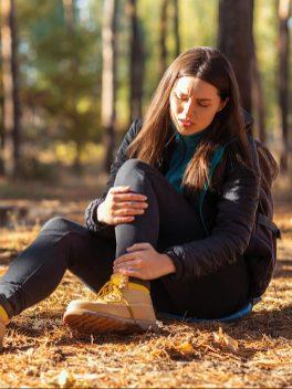Frau im Wald sitzt ab Boden und hält sich den Knöchel. Verstaucht, umgeknickt. Herbst. Gesund durch den Herbst