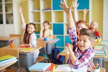 Kinder in Schulklasse heben die Hand. Glückliche Kinder. So gelingt der Schulstart