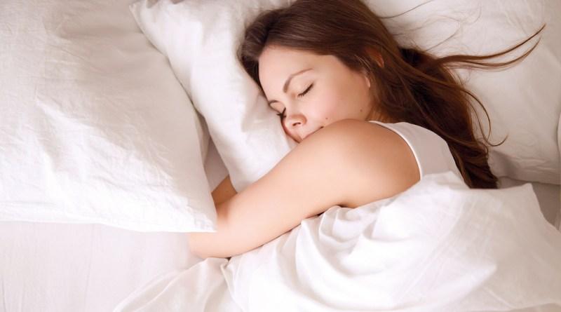Vogelperspektive: Junge Frau schläft gut im Bett mit weißen Laken. Frau umarmt den Polster. erholsamer Schlaf
