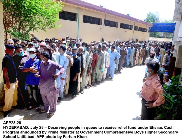 HYDERABAD: July 28 – Deserving people in queue to receive relief fund under Ehsaas Cash Program announced by Prime Minister at Government Comprehensive Boys Higher Secondary School Latifabad. APP photo by Farhan Khan