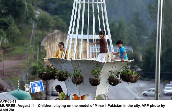 MURREE: August 11 - Children playing on the model of Minar-i-Pakistan in the city. APP photo by Abid Zia