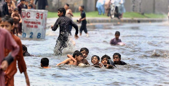 RAWALPINDI: August 25 - Children playing in rain water accumulated at Rawal Road after heavy monsoon rain in the city. APP photo by Abid Zia