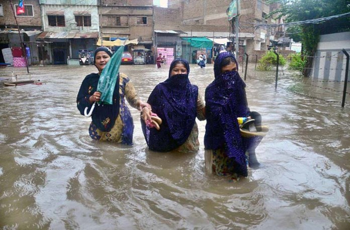 HYDERABAD: August 25 – Women passing through accumulated rain water at Latifabad Unit Number 02 after heavy rain in the city. APP photo by Farhan Khan