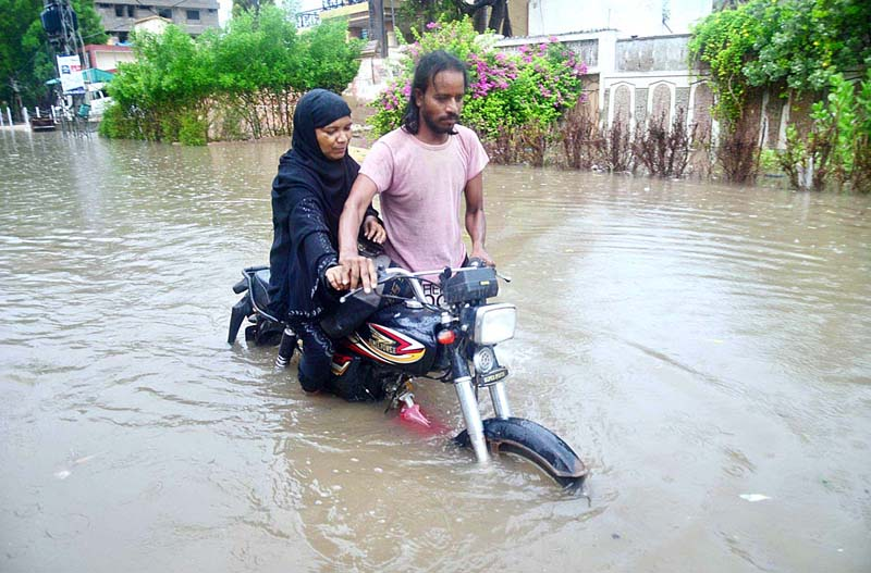 HYDERABAD: August 25 – Motorcyclist with lady passing through accumulated rain water at Latifabad after heavy rain in the city. APP photo by Farhan Khan