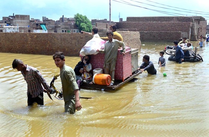 HYDERABAD: August 26 – Residents of Mehar Ali Shah Colony shifting household goods to safe place as houses half submerged in water in rain affected area. APP photo by Farhan Khan