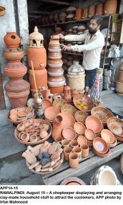 RAWALPINDI: August 15 – A shopkeeper displaying and arranging clay-made household stuff to attract the customers. APP photo by Irfan Mahmood